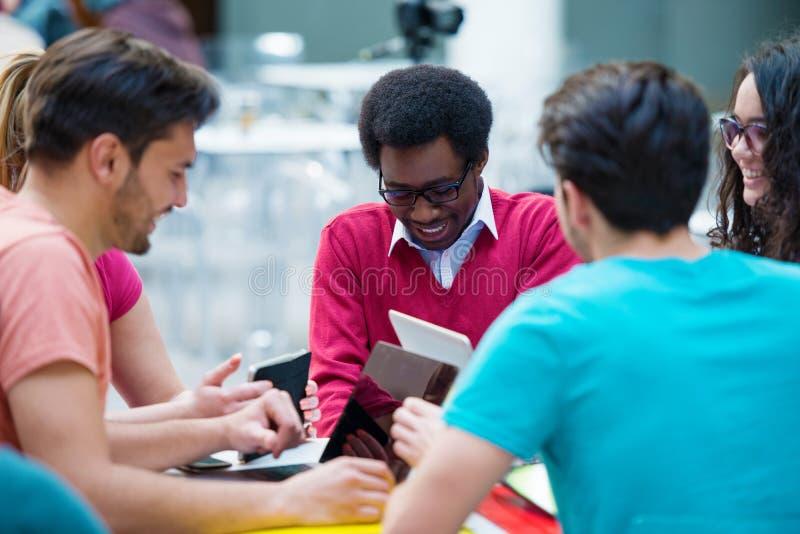 Multiraciale groep jonge studenten die samen bestuderen Hoge die hoek van jongeren wordt geschoten die bij de lijst zitten stock foto's
