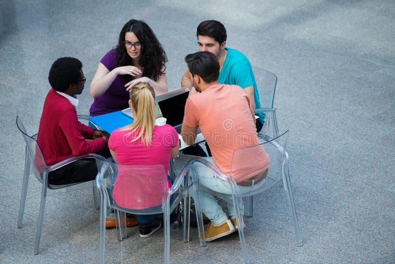 Multiraciale groep jonge studenten die samen bestuderen Hoge die hoek van jongeren wordt geschoten die bij de lijst zitten royalty-vrije stock foto