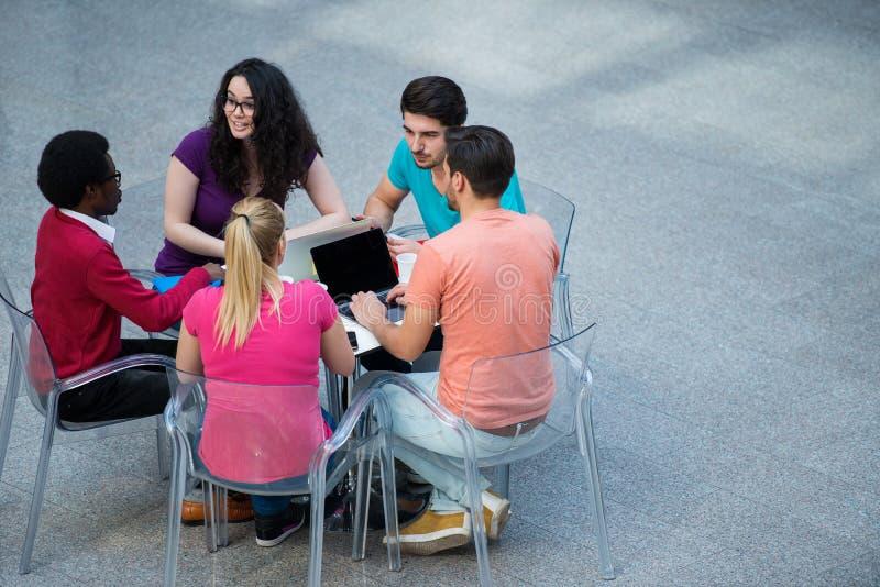 Multiraciale groep jonge studenten die samen bestuderen Hoge die hoek van jongeren wordt geschoten die bij de lijst zitten stock fotografie