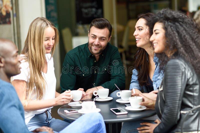 Multiraciale groep van vijf vrienden die een koffie hebben samen stock afbeelding