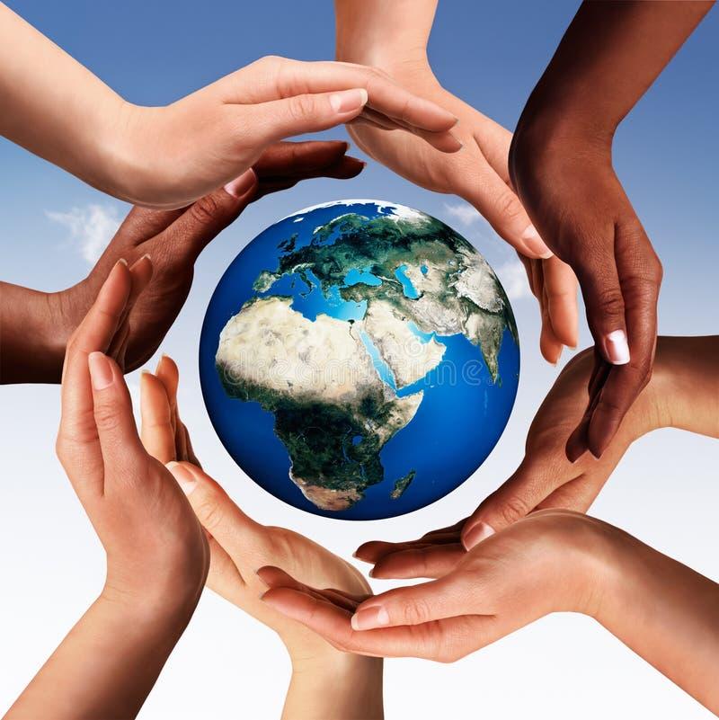 Multiraciale handen die een cirkel maken samen rond de wereld glob stock fotografie