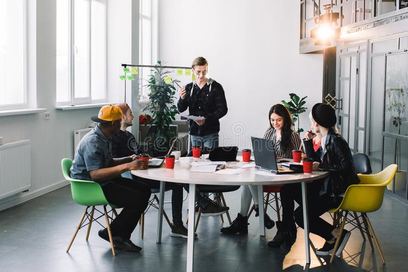 Multiraciale jonge creatieve mensen in modern bureau De groep jonge bedrijfsmensen werkt samen met laptop royalty-vrije stock afbeelding