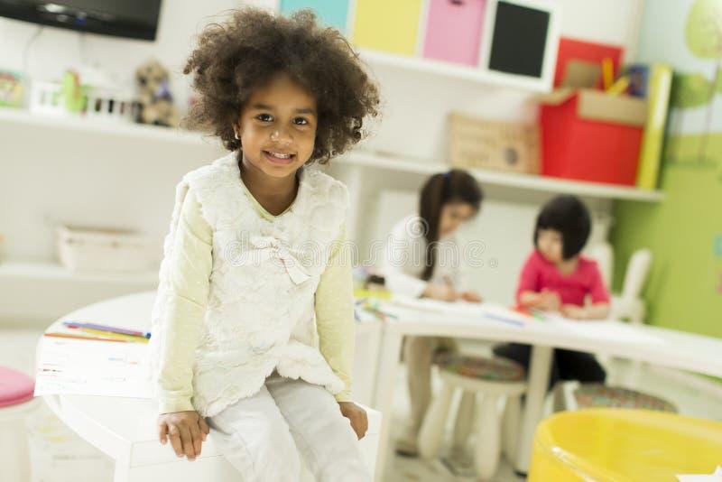 Multiraciale kinderen die in de speelkamer trekken stock foto
