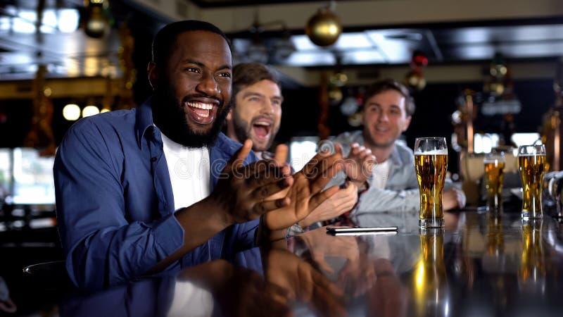 Multiraciale mannelijke vrienden die favoriete teamoverwinning vieren, die van tijd in bar genieten royalty-vrije stock foto's