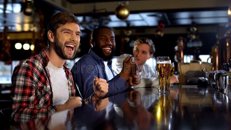 Multiraciale mannelijke vrienden die overwinning vieren, die voor favoriet team in bar toejuichen royalty-vrije stock afbeeldingen