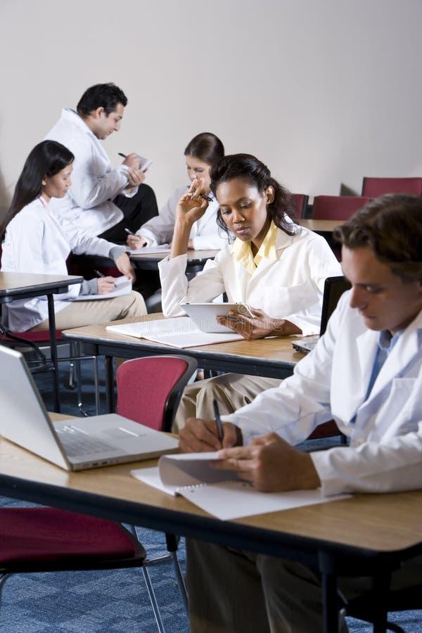 Multiraciale medische studenten die in klaslokaal bestuderen stock foto