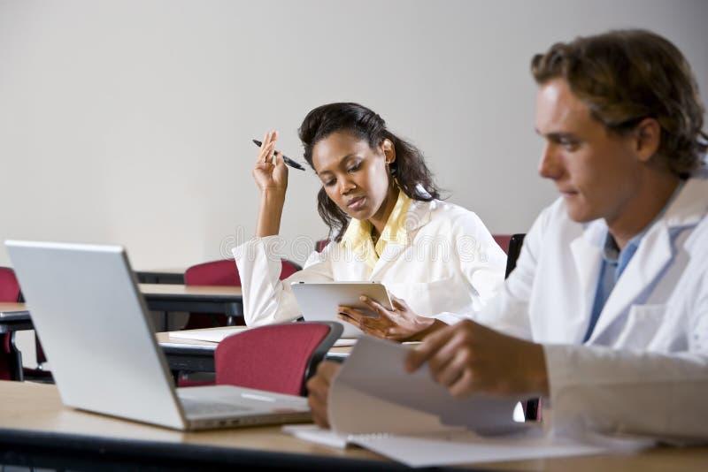 Multiraciale medische studenten die in klaslokaal bestuderen stock afbeeldingen