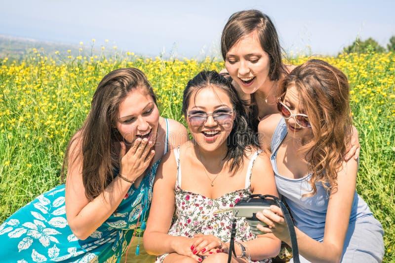 Multiraciale meisjes bij plattelandspicknick het letten op foto's royalty-vrije stock foto