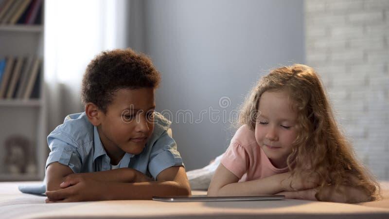 Multiraciale vrienden die op beeldverhalen op tablet letten samen, onderwijsprogramma stock foto