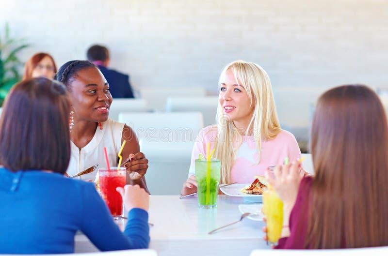 Multiraciale vrouwelijke vrienden die van maaltijd in restaurant genieten royalty-vrije stock afbeeldingen