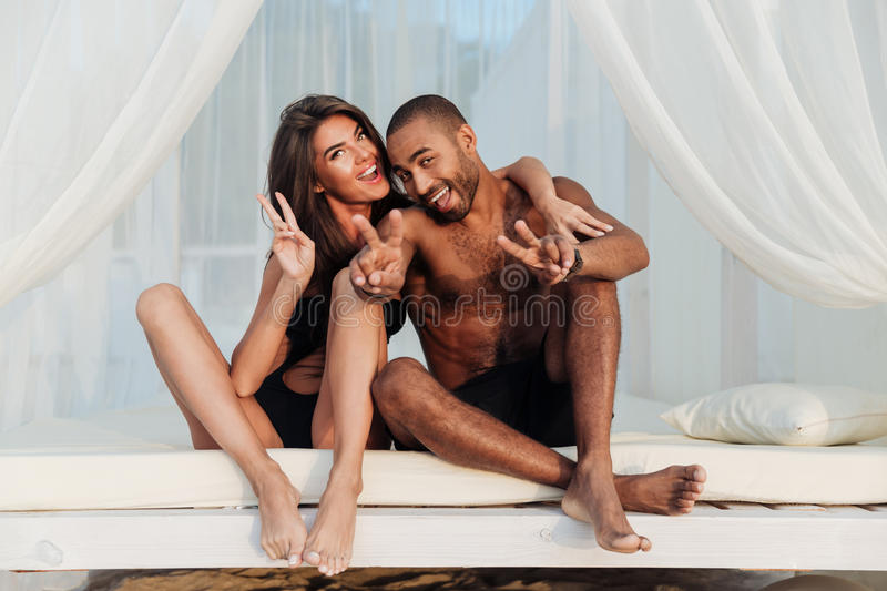 Multircial smiling couple having fun on the beach bed. Lovely multircial smiling couple in love having fun on the beach bed and showing v sign royalty free stock photography
