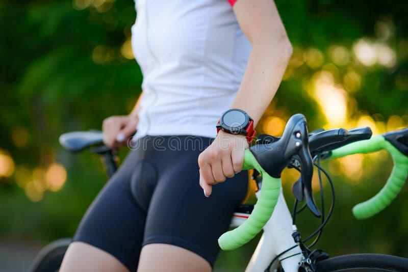 Multisport Smartwatch σε ετοιμότητα του οδικού ποδηλάτη που στηρίζεται με το ποδήλατο στο ηλιοβασίλεμα Κινηματογράφηση σε πρώτο π στοκ εικόνες