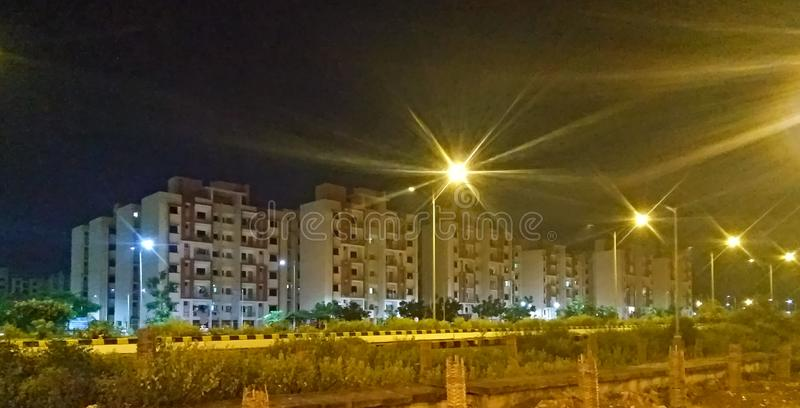 Multistorey buildings, street lights, road and green trees of a housing society in a city in the night, night mode photography. High, colourful, bright royalty free stock photos