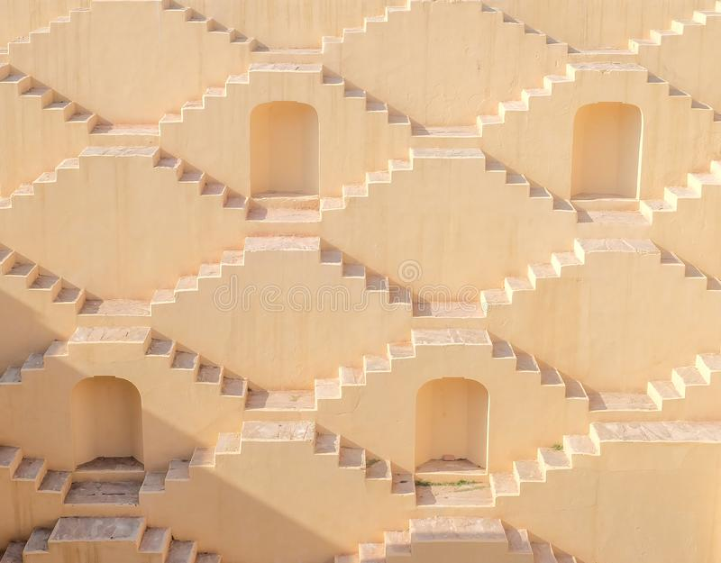 Multistory stairs of a step-well in Jaipur, India. Four recessed doorways & cream-colored zigzag stairs of Panna Meena Ka Kund, an 8-story step-well near Amber royalty free stock photo