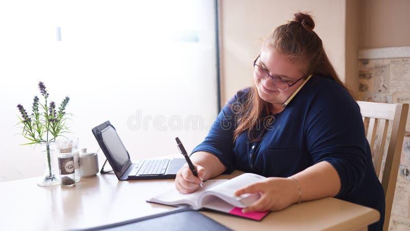 Multitarefa caucasiano da mulher de negócio do tamanho positivo em um café brilhante imagem de stock
