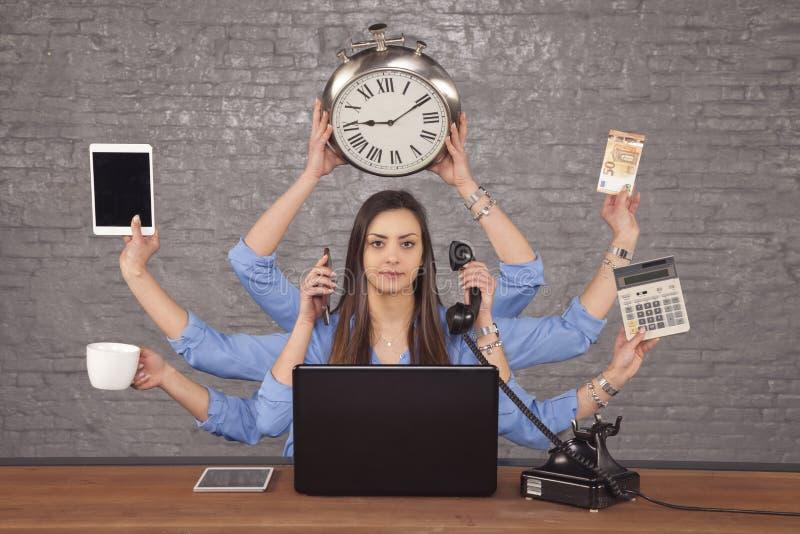 Multitask affärskvinna som sitts på skrivbordet i kontoret, begreppsnolla arkivfoton