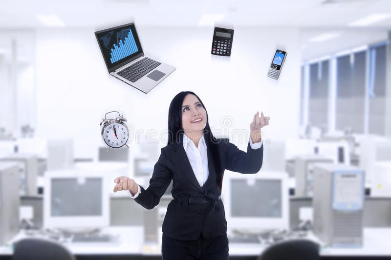 Multitasker businesswoman using laptop, calculator, phone, clock royalty free stock images