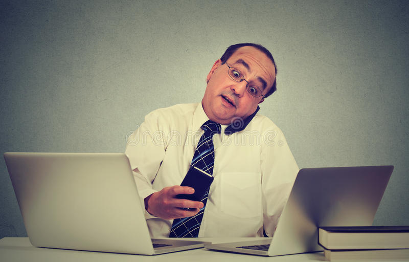 Multitasking business man working at office desk. Busy life of company manager. Multitasking middle aged business man working at his office desk isolated on gray stock photography