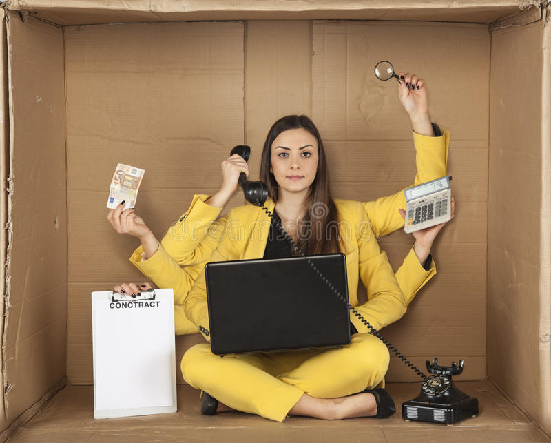 Multitasking businesswoman siting in the box office royalty free stock image
