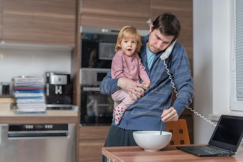 Multitasking father is babysitting and working at home stock photo
