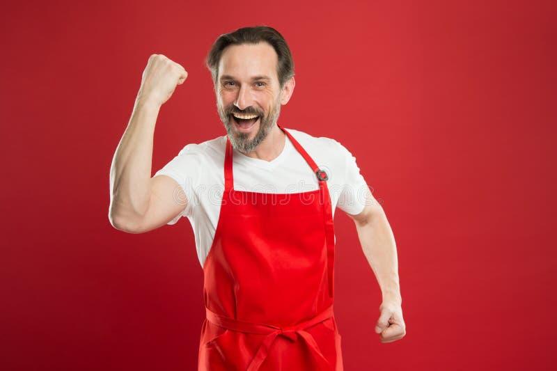 Multitasking jest szefami kuchni gemowymi Cook z brody i wąsy czerwieni tłem Mężczyzny dojrzały kucbarski pozuje kulinarny fartuc fotografia stock