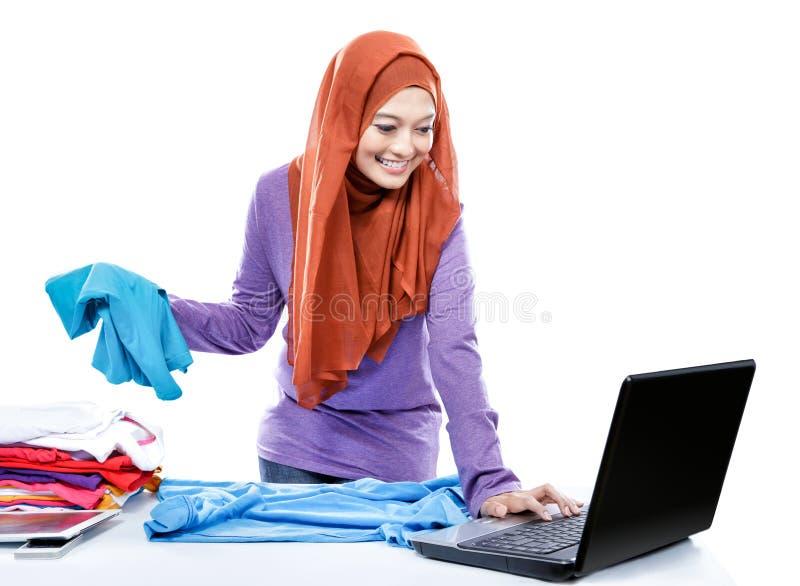 Multitasking młoda kobieta jest ubranym hijab składa czystego odzieżowego whi obraz stock