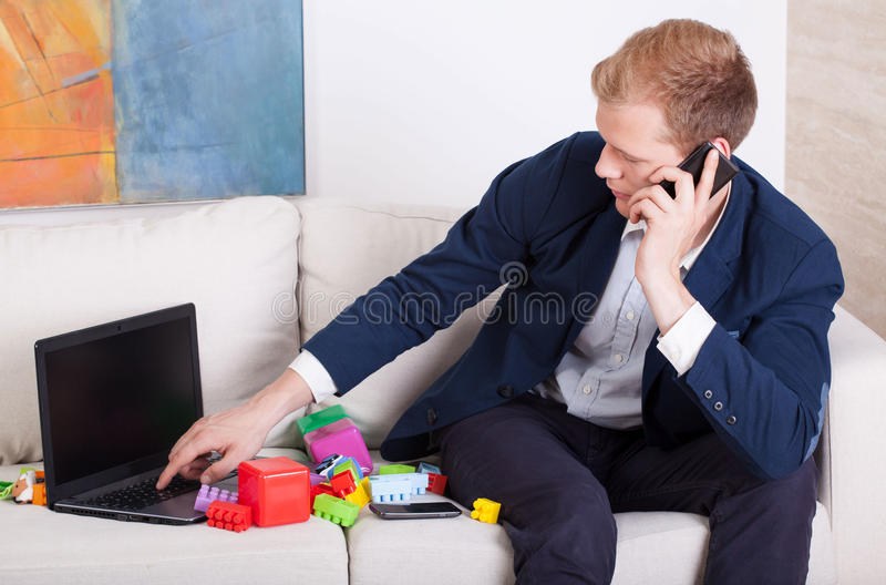 Multitasking man. Father and businessman during work stock images