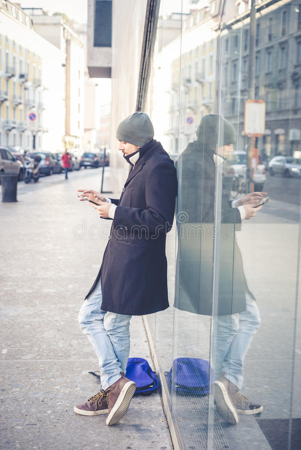 Multitasking man using tablet, laptop and cellhpone. Connecting wifi in the city street urban royalty free stock photography
