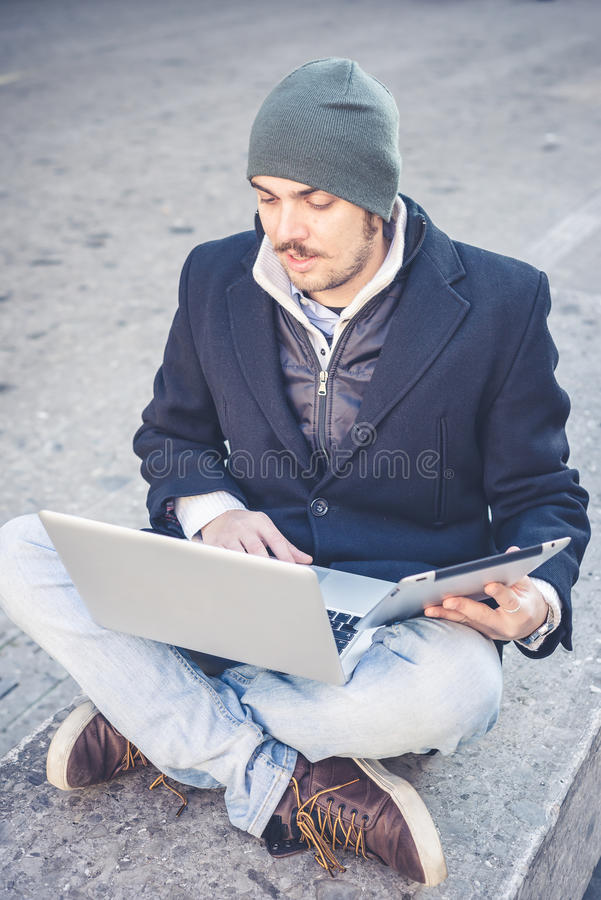 Multitasking man using tablet, laptop and cellhpone. Connecting wifi in the city street urban royalty free stock images