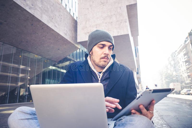 Multitasking man using tablet, laptop and cellhpone. Connecting wifi in the city street urban royalty free stock photos