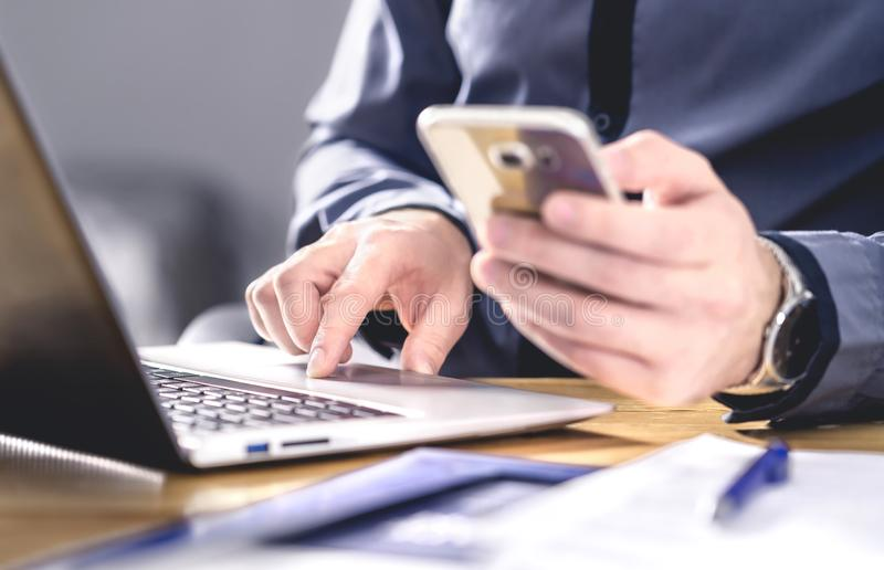 Multitasking and mobile technology. Busy workaholic business man using phone and laptop. Entrepreneur working hard with smartphone stock image