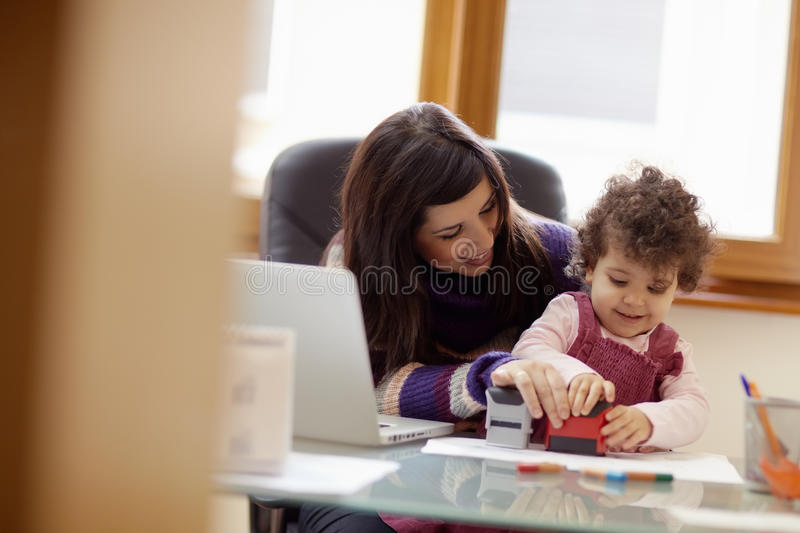 Multitasking mother with her daughter stock photos