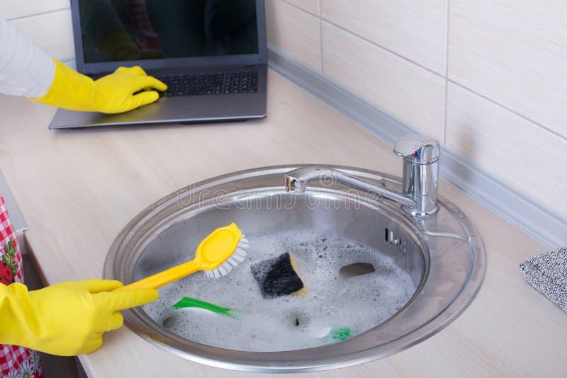 Multitasking pojęcie Kobiety cleaning działanie na laptopie i zlew obraz stock