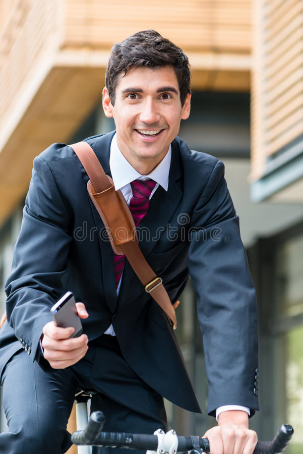 Multitasking young businessman riding a bicycle to work stock photo