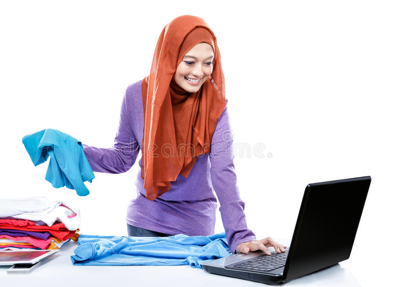 Multitasking young woman wearing hijab folding clean clothes whi stock image