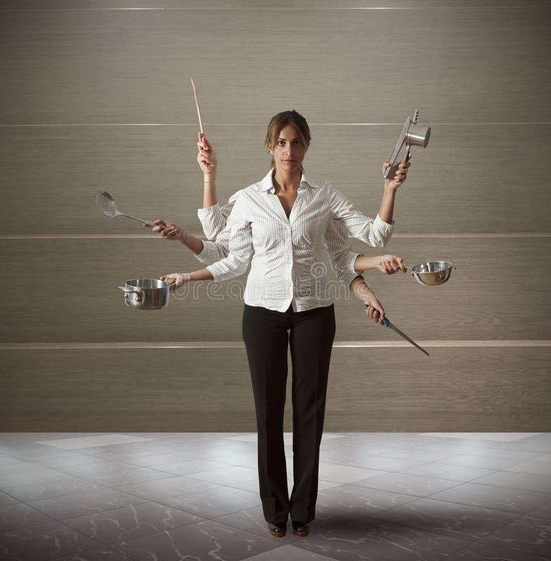 Multitaskingkvinna i kök royaltyfria bilder
