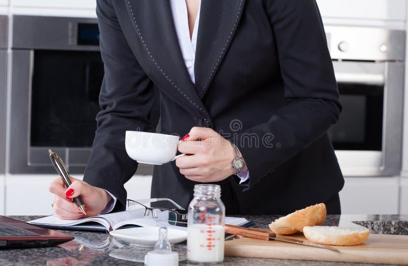 Multitaskingkvinna i kök royaltyfri foto