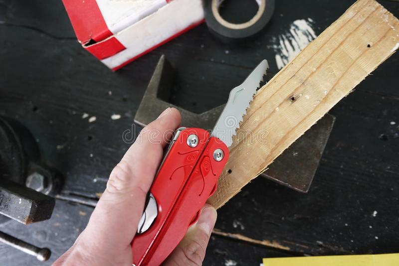 Multitool with a variety of devices. In this device, in the form of a conventional penknife you have a lot of items. Knife, saw, scissors, several screwdrivers royalty free stock photos