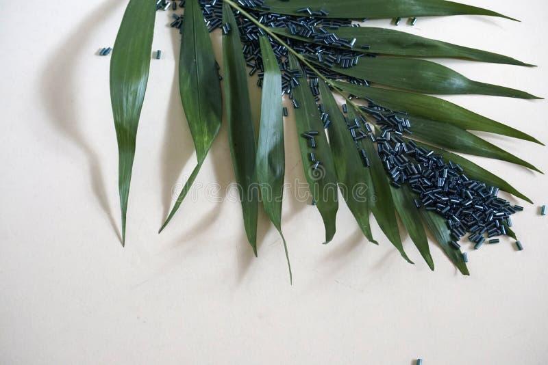 Multitude of green blue tubular toho beads and green leaf . Multitude of green blue tubular toho beads and green leaf on light cream background. Beads used for stock photo