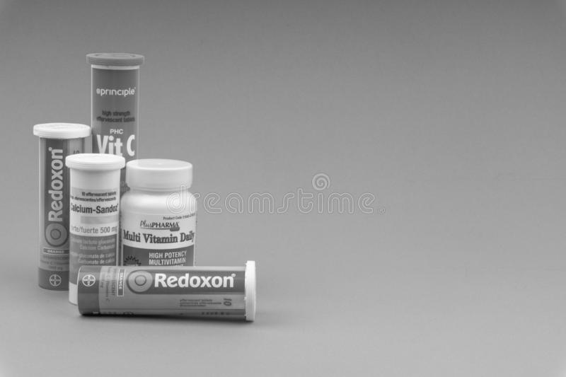 Multivitamin tablets and Vitamin C container on black and white. KUALA LUMPUR, MALAYSIA - APRIL 15, 2019 : Multivitamin tablets and Vitamin C container on black royalty free stock image