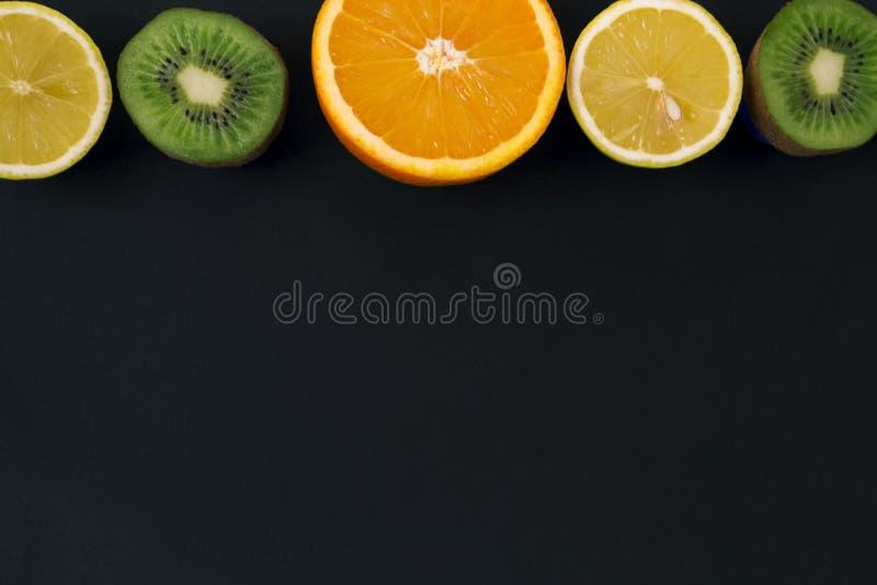multivitamins Υπόβαθρο του πορτοκαλιού, του λεμονιού και του ακτινίδιου φρούτα σε ένα μαύρο υπόβαθρο στοκ εικόνες