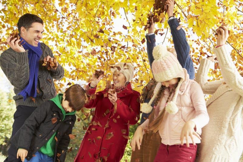 Multl-Generations-Familien-werfende Blätter in Autumn Garden lizenzfreie stockfotografie
