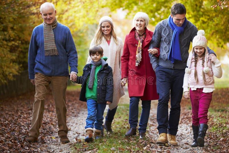 Multl utvecklingsfamilj som promenerar Autumn Path royaltyfri bild
