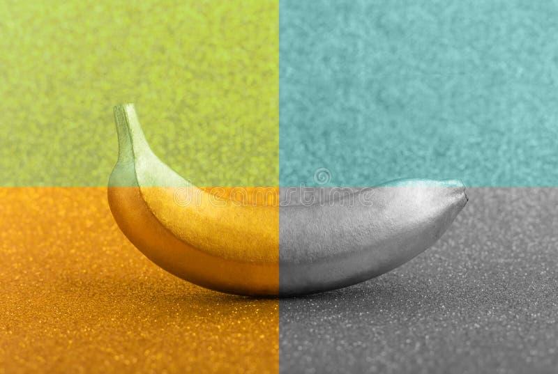 Multy上色了在明亮的闪烁或淡光背景的金属食物,金黄和银色香蕉 时髦热带创造性的概念 图库摄影