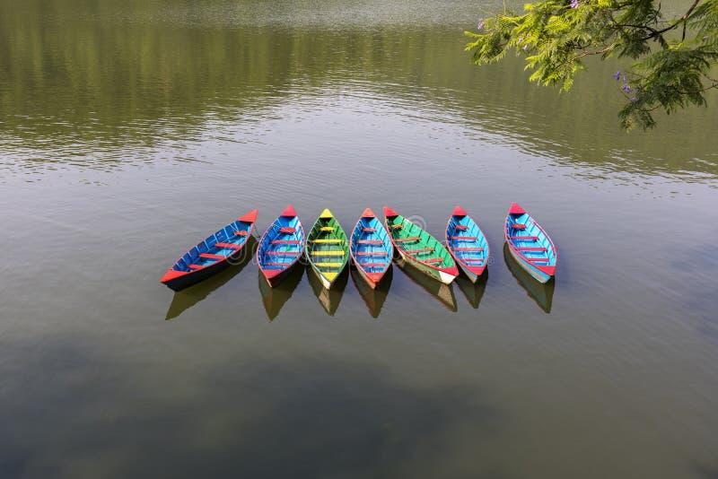 Multy coloreó los barcos que remaban de la madera en el lago Nepal Fewa foto de archivo