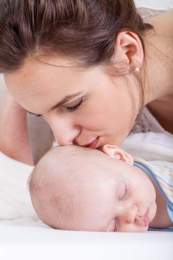 Mum całuje jej nowonarodzonego dziecka obraz stock