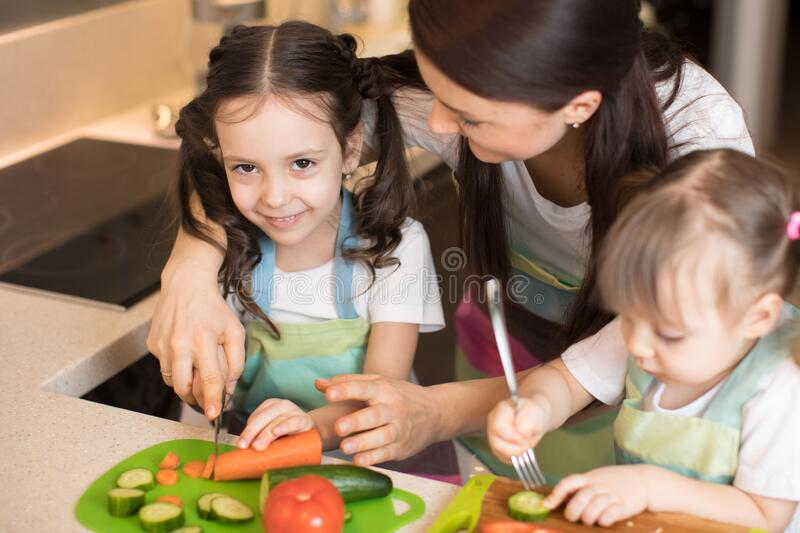 Mum chopping vegetables with children daughters in a family home kitchen. stock photos