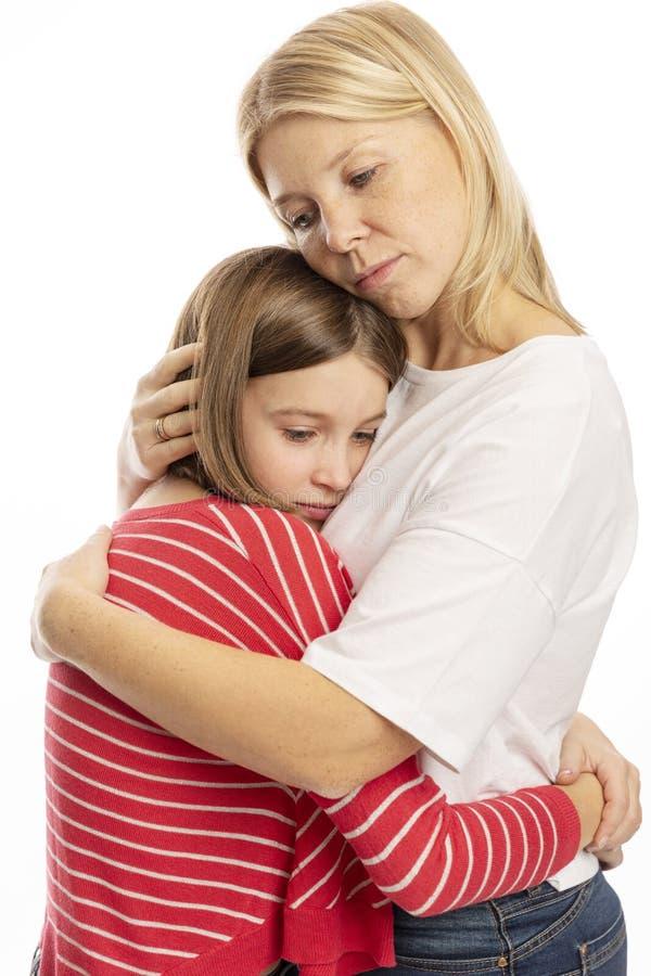 Mum com uma filha do adolescente que abraça, fundo branco fotos de stock