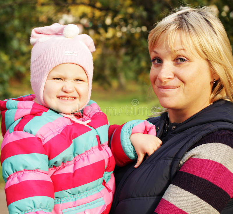 Mum with a daughter in autumn park stock photography