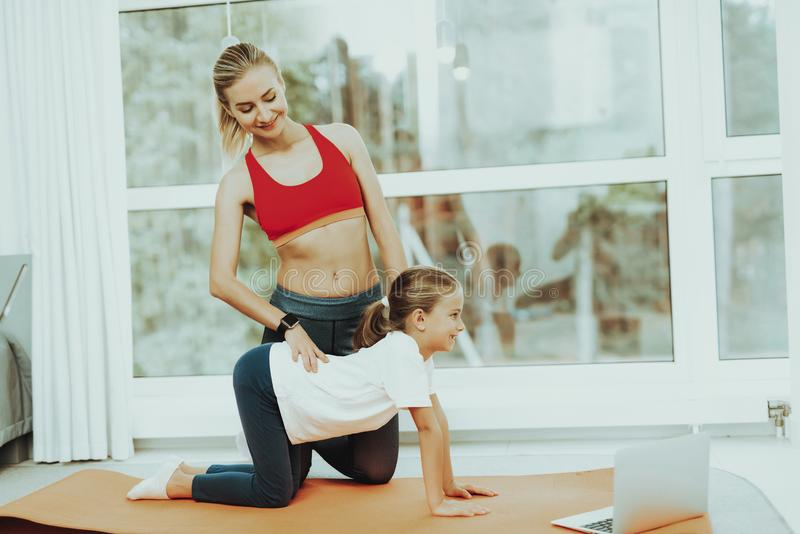 Mum And Daughter Back Stretching. Laptop Screen. Active Lifestyle. Relaxing Together. Doing Fitness At Home. Holiday Leisure. Body Balance. Sport Exercise stock photo
